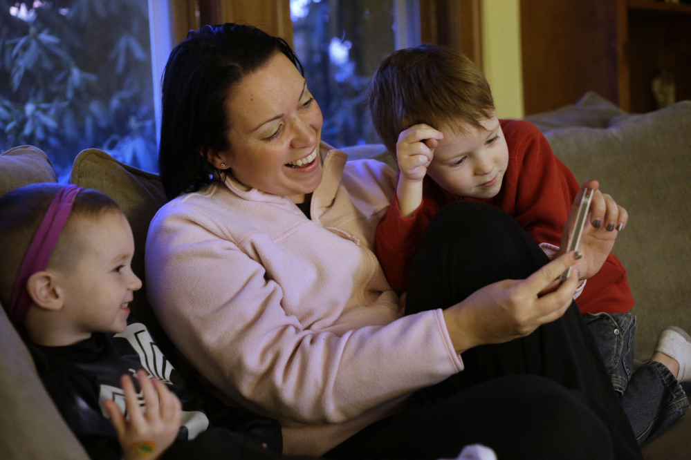 Julie Young, a Boston-based behavioral analyst, center, sits with her sons Nolan, 3, left, and Jameson, 4, while looking at a smart phone at their home, in Boston.