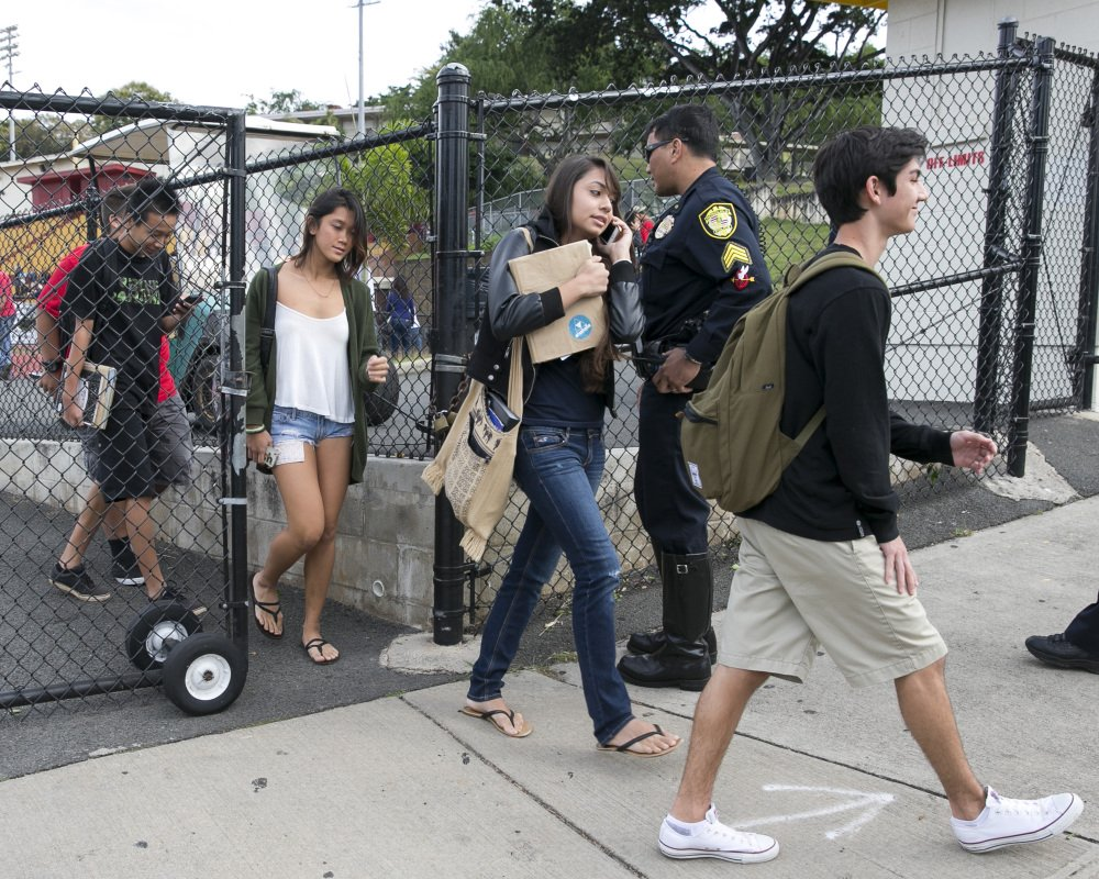 Students leave Roosevelt High School in Honolulu on Tuesday after a police officer shot a 17-year-old runaway in the wrist at the high school after the teen cut one officer with a knife and punched two others, authorities said.