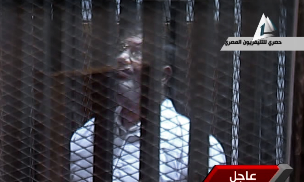 In this image taken from Egypt State TV, Egypt's toppled President Mohammed Morsi stands inside a glass-encased metal cage in a courtroom in Cairo on Tuesday.