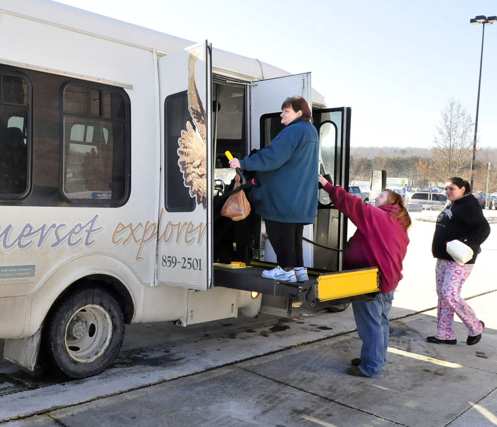 ALL ABOARD: Somerset Explorer bus driver Rhonda Watson, center, helps passengers to board the bus during a stop at Hannaford supermarket in Skowhegan.