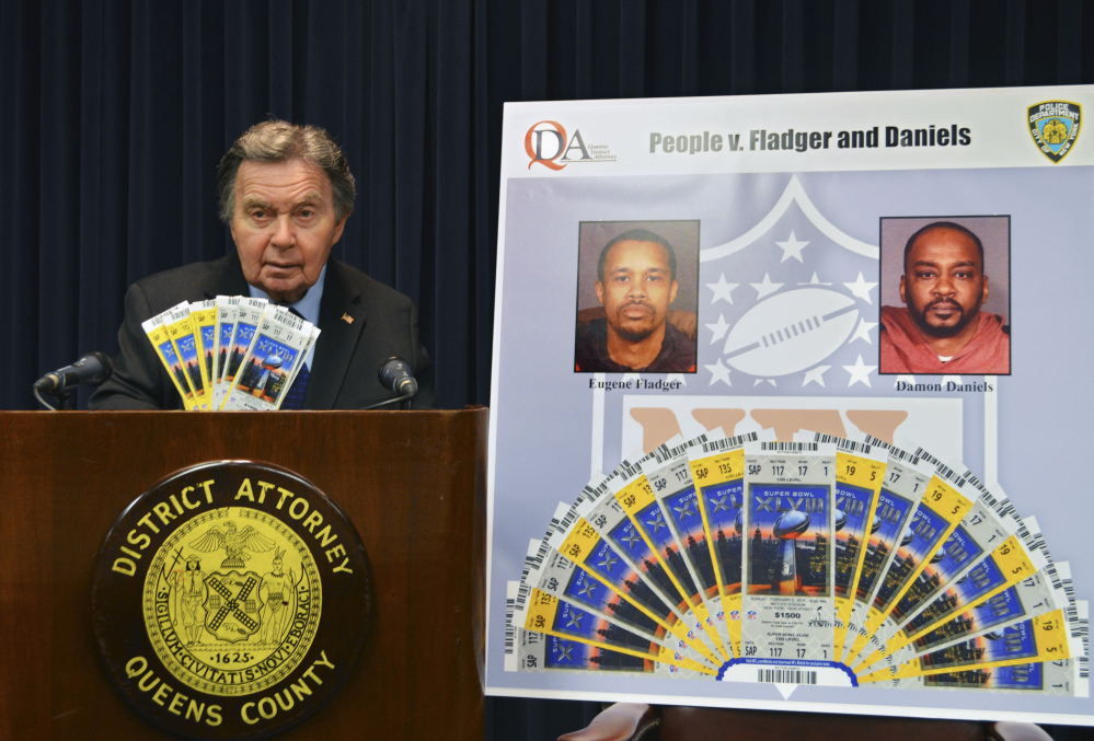Richard Brown, Queens County district attorney, displays counterfeit Super Bowl tickets at a news conference Tuesday in New York. Two men made high-quality counterfeit tickets for the Super Bowl and other postseason NFL games and sold them online, authorities said. The men face charges of forgery, possession of forged instruments and other trademark counterfeit charges.