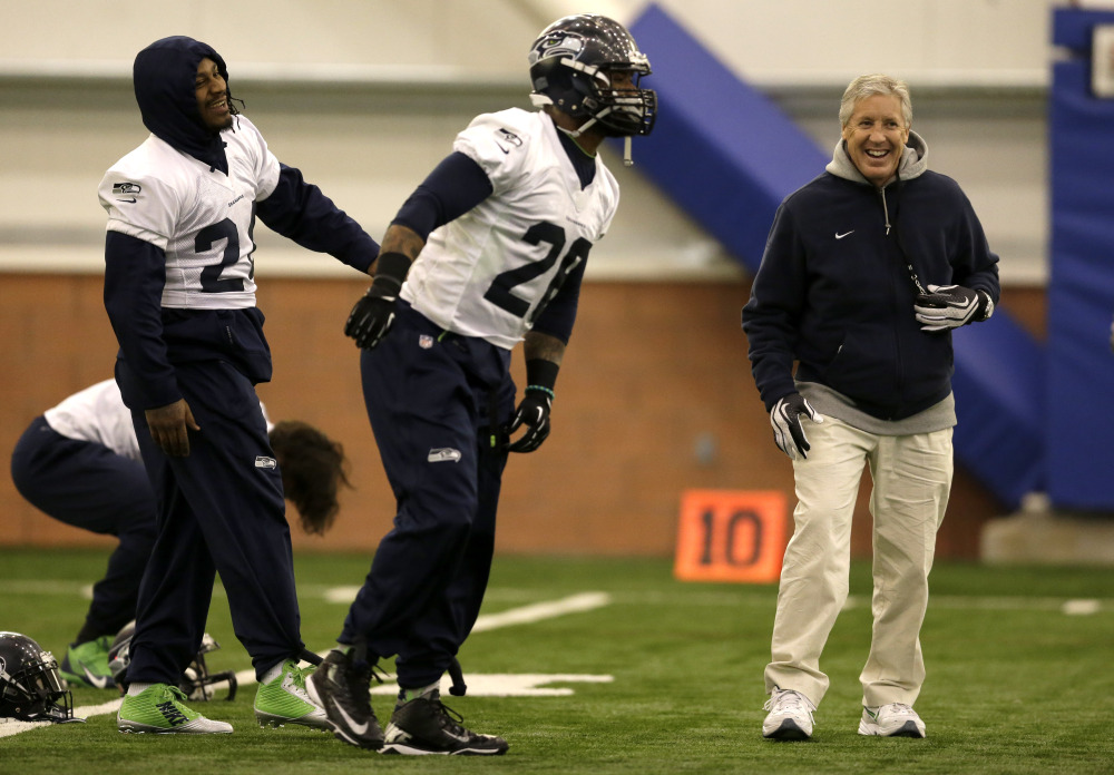 ON THE MOVE: Seattle Seahawks head coach Pete Carroll, right, laughs as running back Marshawn Lynch, left, and fullback Michael Robinson, center, warm up at the start of practice Thursday in East Rutherford, N.J. Carroll and general manager John Schneider have made 839 roster moves during their time in Seattle. The Seahawks and the Denver Broncos are scheduled to play in the Super Bowl XLVIII on Sunday.