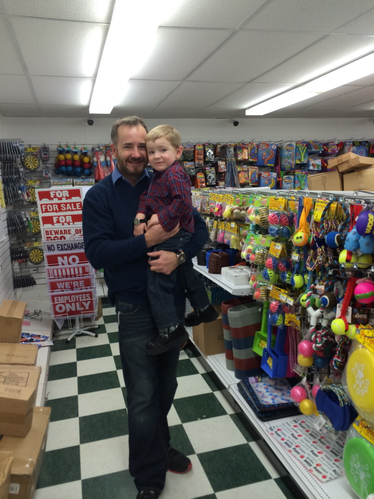 DOLLAR MAN: Thad Barber, owner of the new Dollar Deals variety store on Route 3 in South China, holds his 3-year-old son Tyler at Barber's new store. The variety store is set to open on Feb. 8.