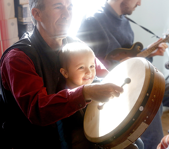 Levi Bannon, 3, helps his father, Dan, play the bodhran, an Irish drum, with the Highland String Trio in the warming hut at the mushers bowl. Besides Celtic music, people enjoyed soups and baked goods from the South Bridgton Congregational Church.