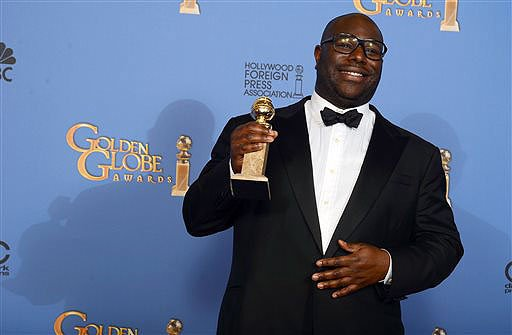 """Steve McQueen poses in the press room with the award for best motion picture - drama for """"12 Years a Slave"""" at the 71st annual Golden Globe Awards on Sunday."""