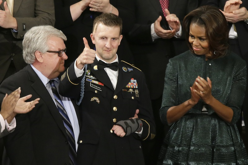 Army Ranger Sgt.1st Class Cory Remsburg acknowledges applause from first lady Michelle Obama and others during President Barack Obama's State of the Union address on Capitol Hill in Washington, Tuesday Jan. 28, 2014.