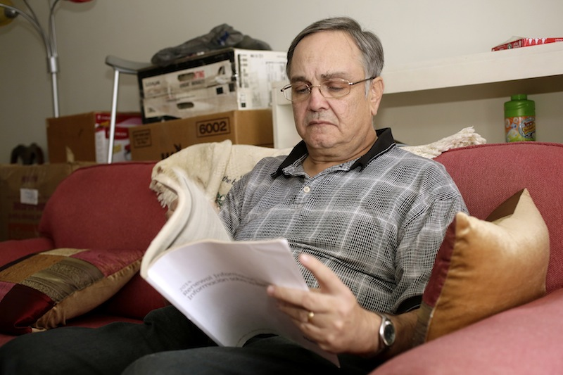 """Howard Kraft looks over healthcare information in his Lincolnton, N.C. home Monday, Dec. 30, 2013. All things good, bad and unpredictable converge Jan. 1 for President Barack Obama's health care overhaul as the law's major benefits take effect, along with an unpopular insurance mandate and a real risk of more nerve-wracking disruptions to coverage. For some, the changes bring big improvements, including Kraft. A painful spinal problem left him unable to work as a hotel bellman. But he's got coverage because federal law now forbids insurers from turning away people with health problems. """"I am not one of these people getting a policy because I'm being made to,"""" Kraft said. """"I need one to stay alive."""""""
