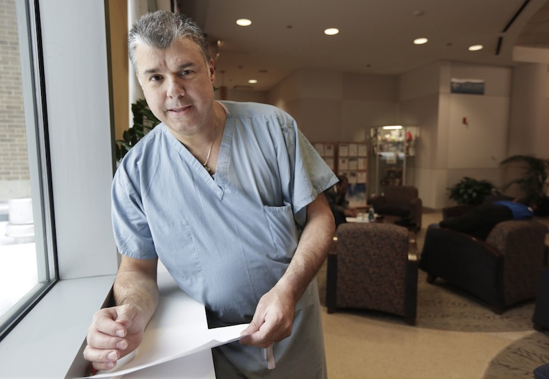 """Dr. John Venetos poses for a photo between surgical procedures Thursday, Jan. 2, 2014, in Chicago. With the full implementation of the nation's new health law that took effect New Year's Day, Venetos described the """"tremendous uncertainty and anxiety"""" among patients calling his office who think they signed up for coverage but haven't received insurance cards yet. Others had insurance policies that were canceled and they aren't sure if their coverage was reinstated after Gov. Pat Quinn decided to allow one-year extensions of canceled plans. The Chicago physician has decided to take a risk and provide care for these patients. """"We feel it's the right thing to do,"""" Venetos said. """"We may end up stuck holding the bag and not getting paid on these claims."""""""