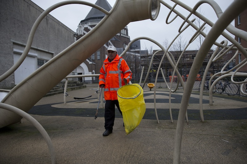 Ramon Mohamed Halim Smits, participant in a pilot project for alcoholics, cleans a playground in Amsterdam's eastern part Wednesday. The city has teamed up with a charity organization in hopes of improving the neighborhood and possibly improving life for the alcoholics. Participants are given beer in exchange for a little work collecting litter, eating a decent meal, and sticking to their schedule.