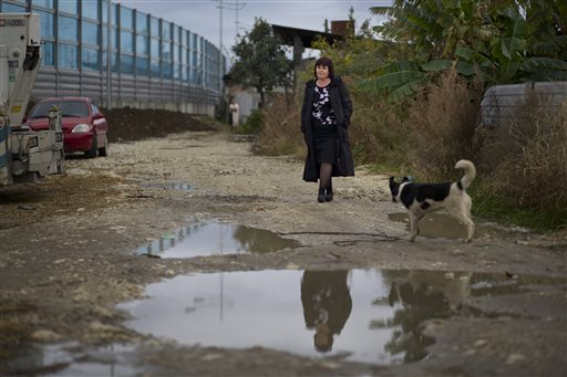 Irina Kharchenko walks in the yard of her house beside the screen separating the yard of her house and a federal highway in the village Vesyoloye outside Sochi, Russia.