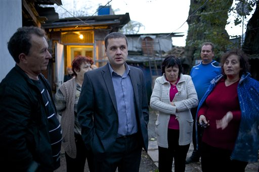 """Igor Zarytovsky, center, and his father Vladimir, left, gather with their neighbors in the yard of the railroad house in the village of Vesyoloye outside Sochi, Russia. Unusual for Russia, Sochi area residents are not only willing to talk to reporters but stop them in the street and invite them over to see """"what the real Sochi looks like."""""""
