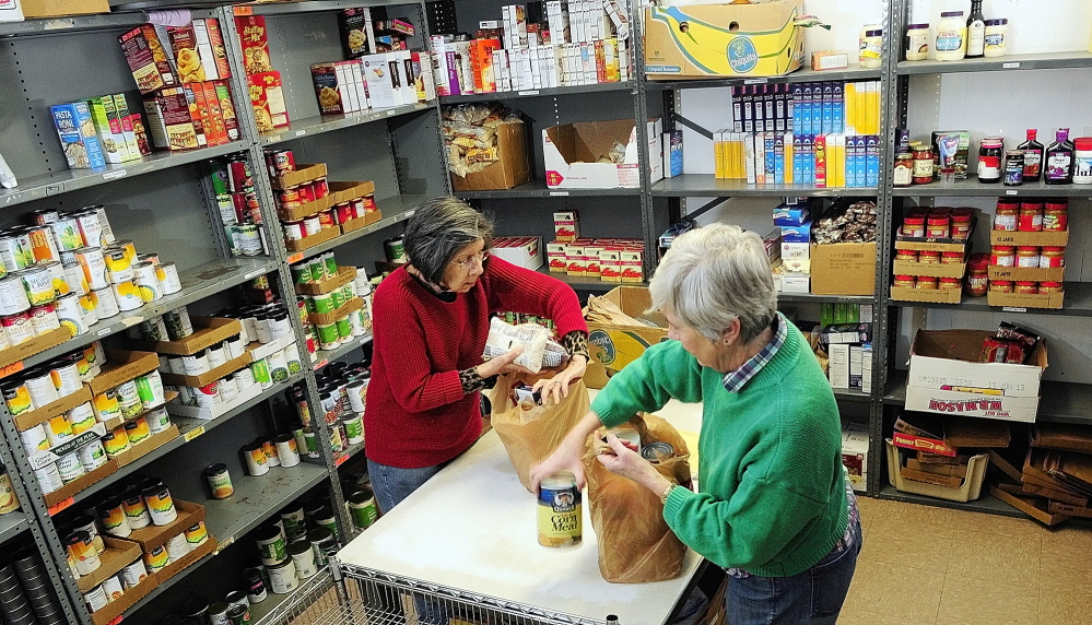 food pantry: Volunteers Elaine Brann, left, and Jeanne Rocque pack groceries for a client on Thursday at the Augusta Food Bank at St. Mark's Episcopal Church in Augusta.