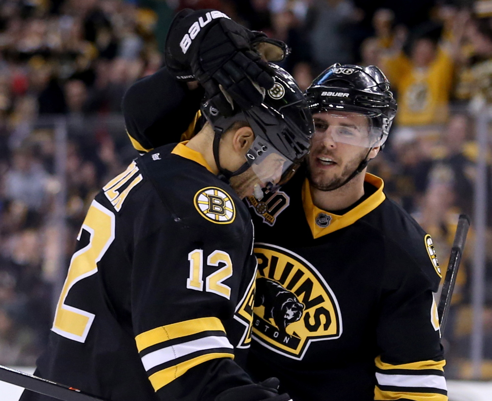 David Krejci, right, is congratulated by Jarome Iginla after scoring a second-period goal Saturday against the Edmonton Oilers at Boston. The Bruins won, 4-0.