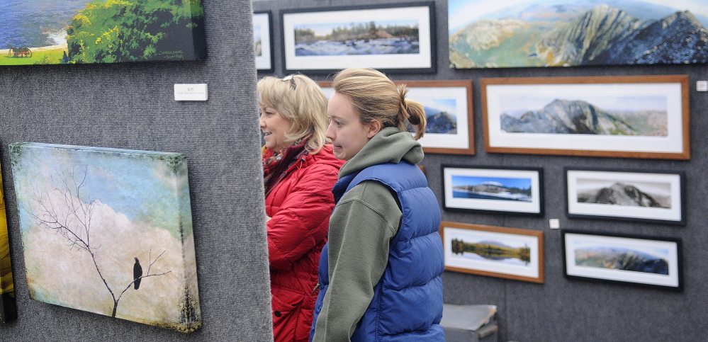 INSPECTORS: Dolly White, left, and her daughter, Becky, inspect panoramic photographs by Scott Perry on Sunday, Feb. 2, 2014, during the annual Cabin Fever Art Show at Longfellow's Greenhouses in Manchester.