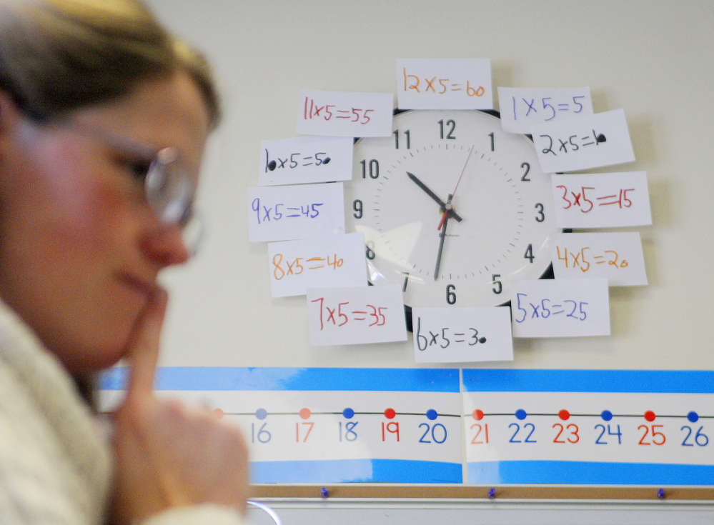 "TALKING NUMBERS: The clock behind Readfield Elementary School third grade teacher Abby Shink is adorned with equations as she listens Wednesday to her class work through an equation with a ""number talk,"" an instructional activity RSU 38 uses to get students to discuss and critique arguments in math, as required in the Common Core State Standards."