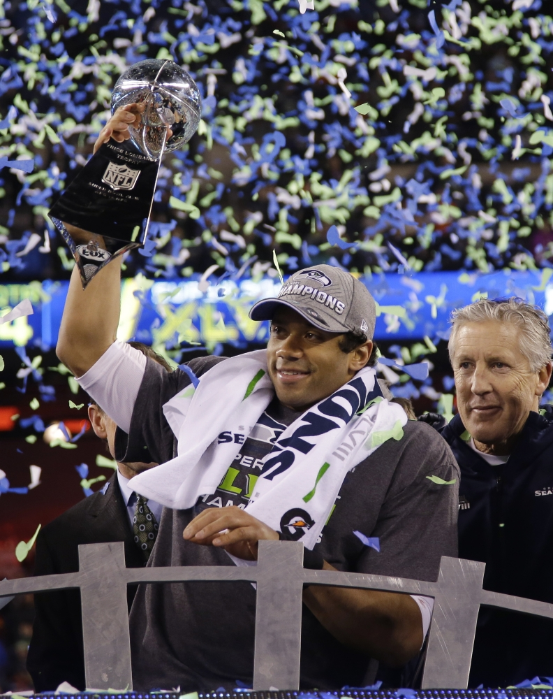 CHAMPIONS: Seattle quarterback Russell Wilson holds the Vince Lombardi Trophy as coach Pete Carroll looks on after the Seahawks defeated the Denver Broncos 43-8 in Super Bowl XLVIII on Sunday in East Rutherford, N.J.