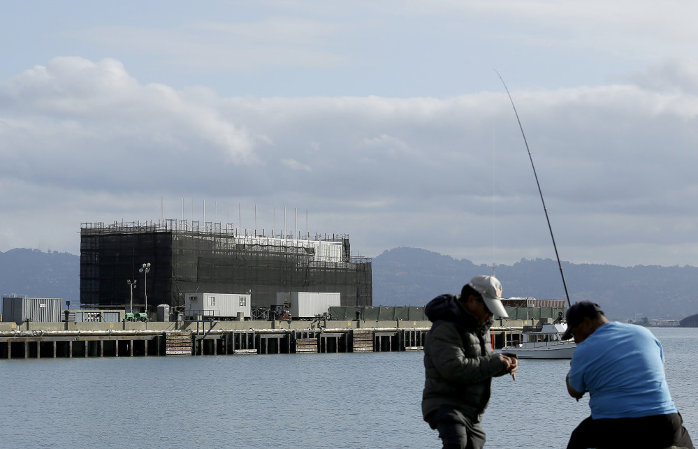 In this Tuesday, Oct. 29, 2013, file photo, two men fish in the water in front of a Google barge on Treasure Island in San Francisco. A state agency says Google must move its mystery barge from a construction site on an island in the middle of the San Francisco Bay because the permits are not in order.