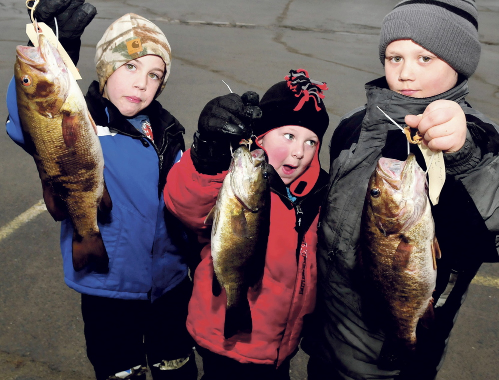 STIFF COMPETITION: From left holding their bass entries are Nikus Stetson, Maddux Duplessis and Zack Knight, all of whom took part in the 23rd annual Children's Ice Fishing Frenzy sponsored by the Oakland Recreation Department and Oakland Lions Club on Sunday, Feb. 2, 2014. First, second and third place prizes were awarded in 10 categories from fish caught in Belgrade Lakes waters.