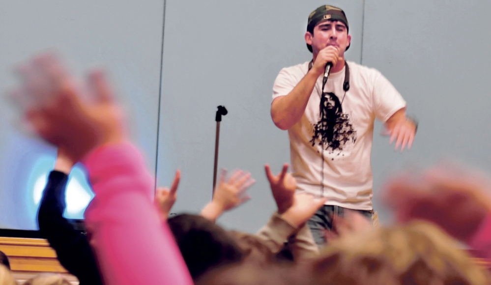 DIG IT: Hip-hop artist Devin Ferreira sings to students clapping their hands to the beat at the Cape Cod Hill School in New Sharon on Monday.