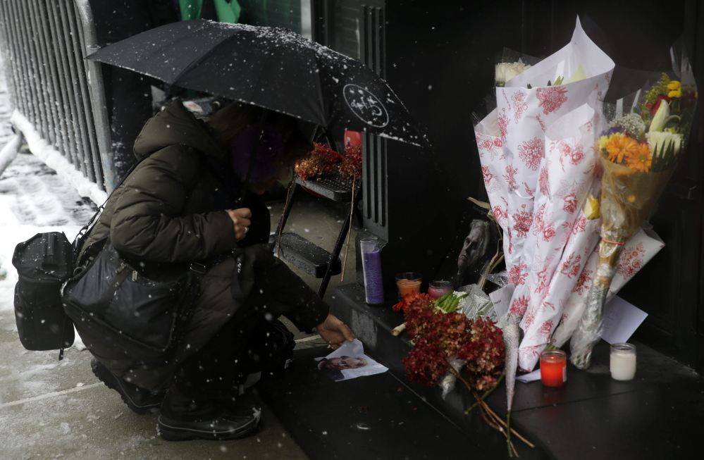 A woman unfolds a picture of Philip Seymour Hoffman on Monday at a makeshift memorial in front of the building where his body was found. Hoffman, 46, was found dead Sunday in his New York apartment of a suspected drug overdose.