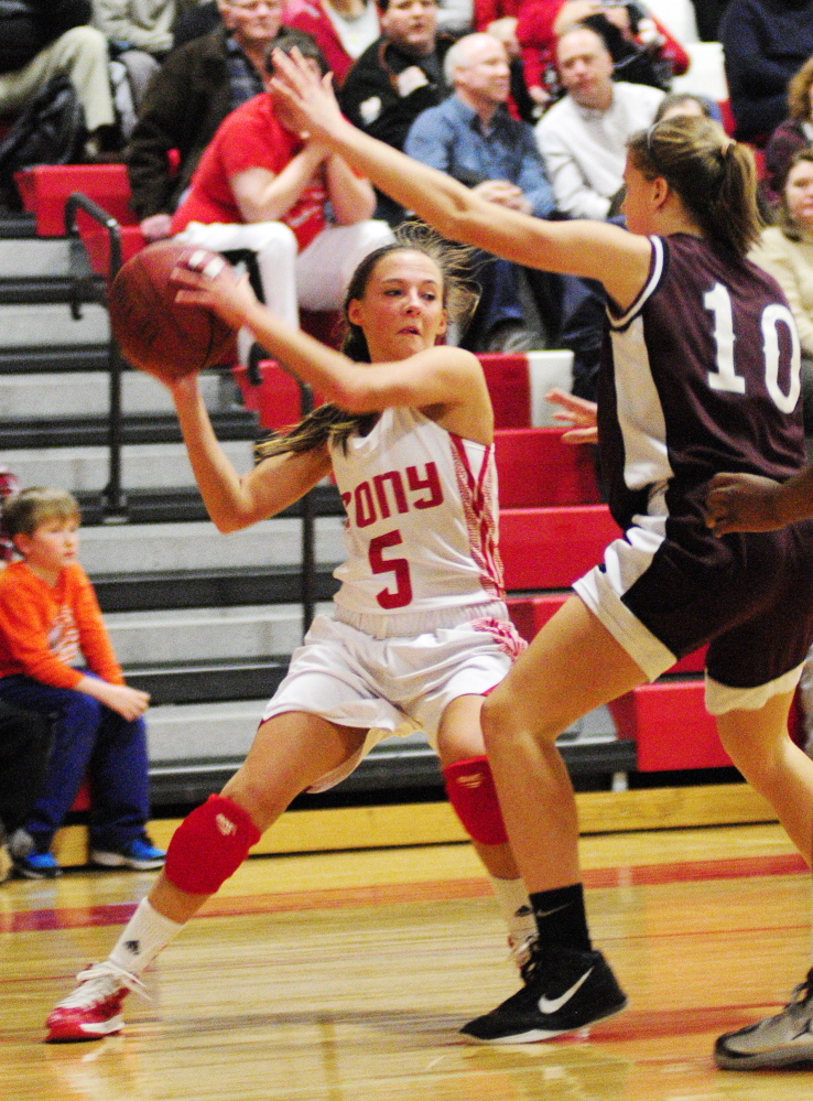 Staff photo by Joe Phelan Cony's Emily Quirion, left, tries to look around Edward Little's Sarah Hammond for a teammate to pass the ball to during a game on Tuesday February 4, 2014 at Cony High School in Augusta.