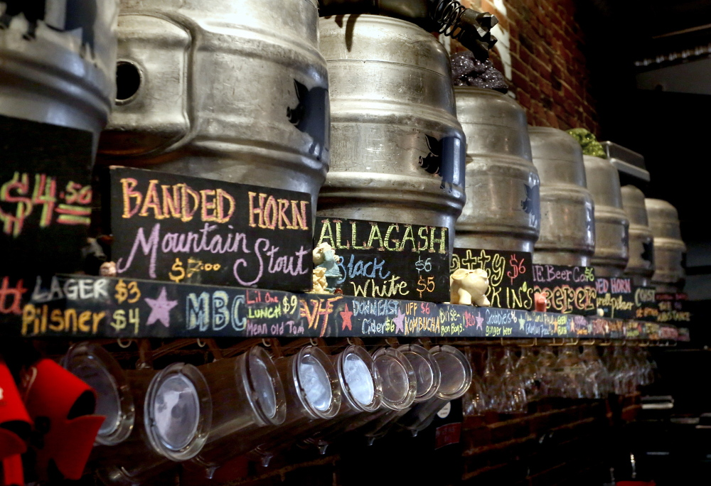 Suppressed detail: Kegs, the contents of which are described by a sign, line the wall at the The Thirsty Pig in Portland. A 1937 state law prohibits posting of alcohol content for beers.