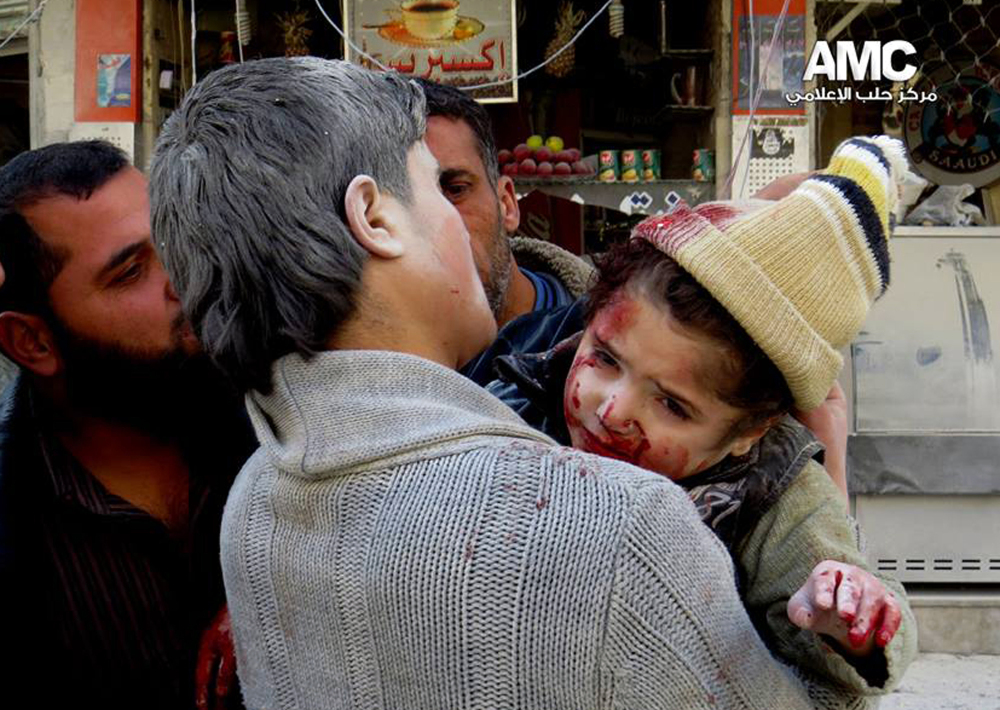 This photo provided by the anti-government activist group Aleppo Media Center (AMC), which has been authenticated based on its contents and other AP reporting, shows a Syrian man carrying a wounded child following a Syrian government airstrike in Aleppo, Syria, Monday.