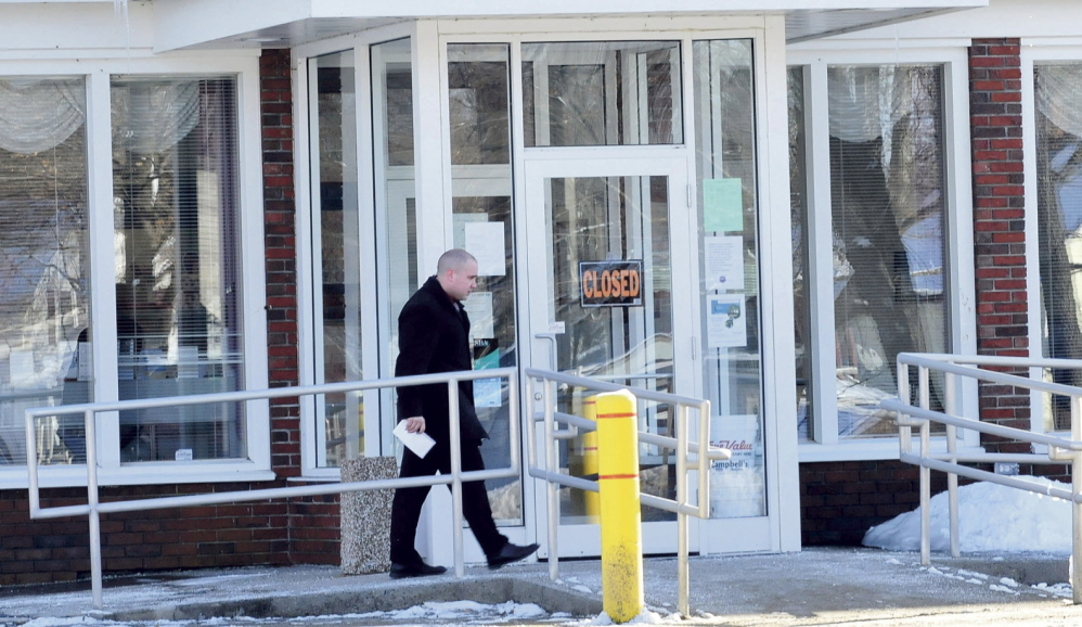CLOSED: A police detective enters the closed Skowhegan Savings bank branch in Bingham after it was robbed Tuesday.