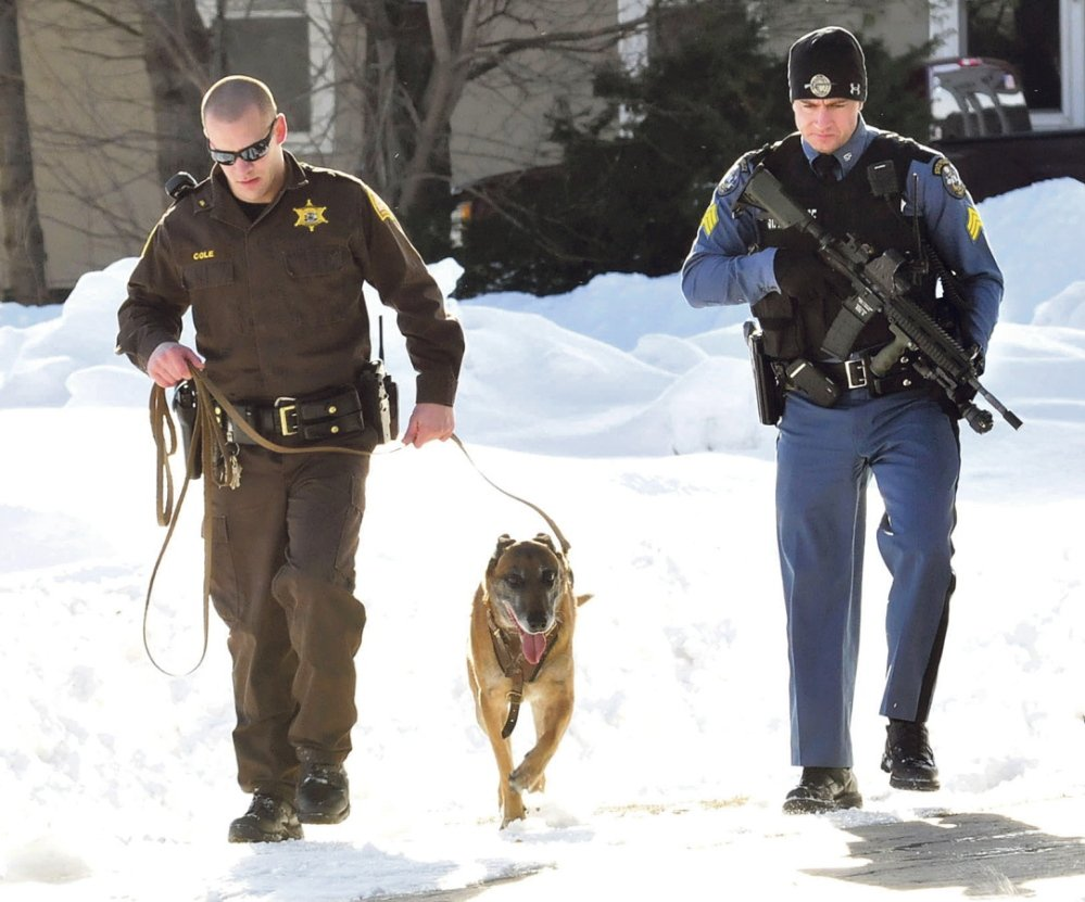 SEARCH: Somerset Sheriff's Deputy David Cole, left, and tracking dog Ruger, along with Trooper Peter Michaud, search the parking lot of Skowhegan Savings bank in Bingham after a man with a hammer robbed the bank on Tuesday.