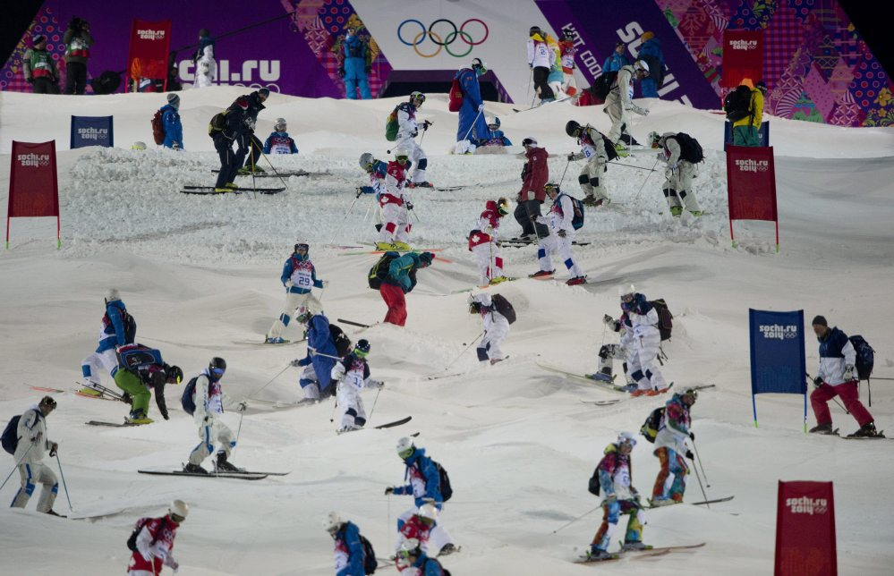Athletes take part in a moguls course inspection Wednesday prior to a freestyle skiing training run at the 2014 Sochi Winter Olympics in Krasnaya Polyna, Russia.