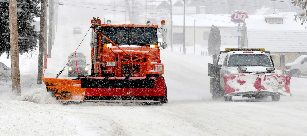 STORM WORK: A Waterville Public Works truck, left, and a private truck were out in force to clear roads during the snow storm on Wednesday.