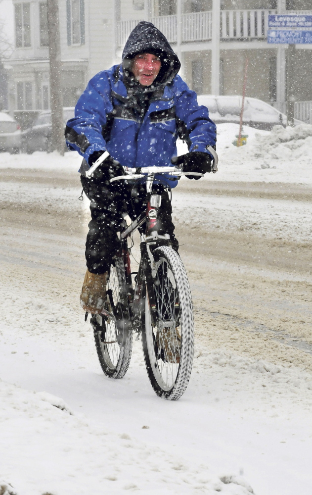 """TWO-WHEEL DRIVE: Danny Hawes manages to keep his bike upright while pedaling in Fairfield on a snowy Wednesday. """"The traction is not good today,"""" Hawes said."""