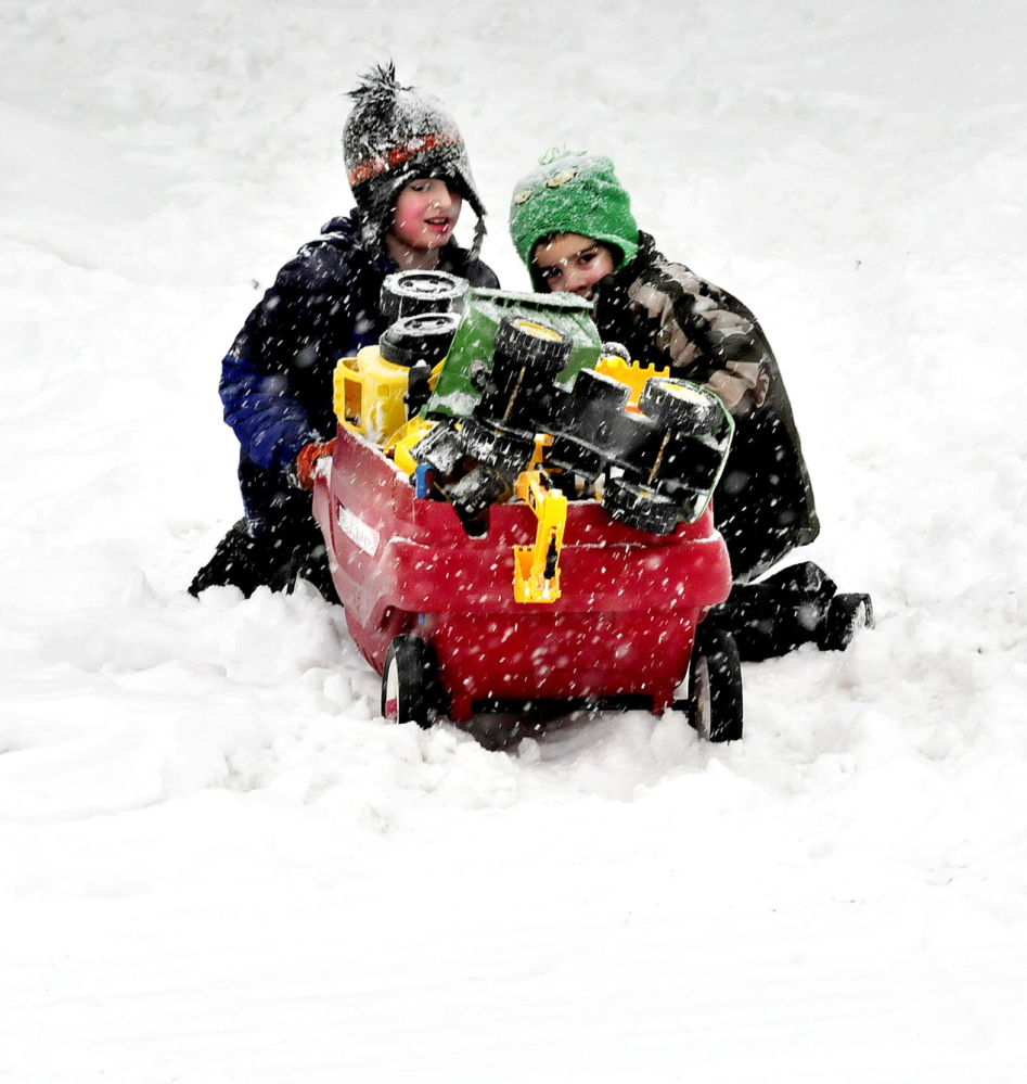 TOUGH GOING: Cameron Meserve, left, and Shaun Watkins struggled in the snow to push a wagon load of toys while playing in the snowstorm on Wednesday.