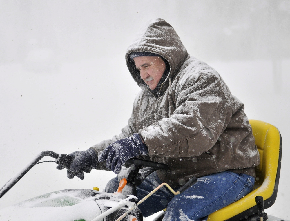 TRAILBLAZER: Bill Canning, adjusts the snow chute on his John Deere tractor plow as he clears a path for the oil delivery driver at a residence he cares for on May Street in Waterville on Wednesday.