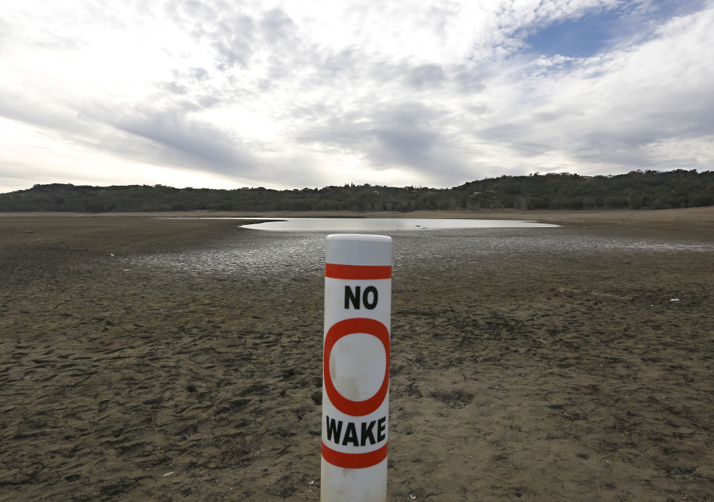 A warning buoy sits on the dry, cracked bed of Lake Mendocino near Ukiah, Calif. Despite recent spot rains, the reservoir is currently only about 37 percent full.