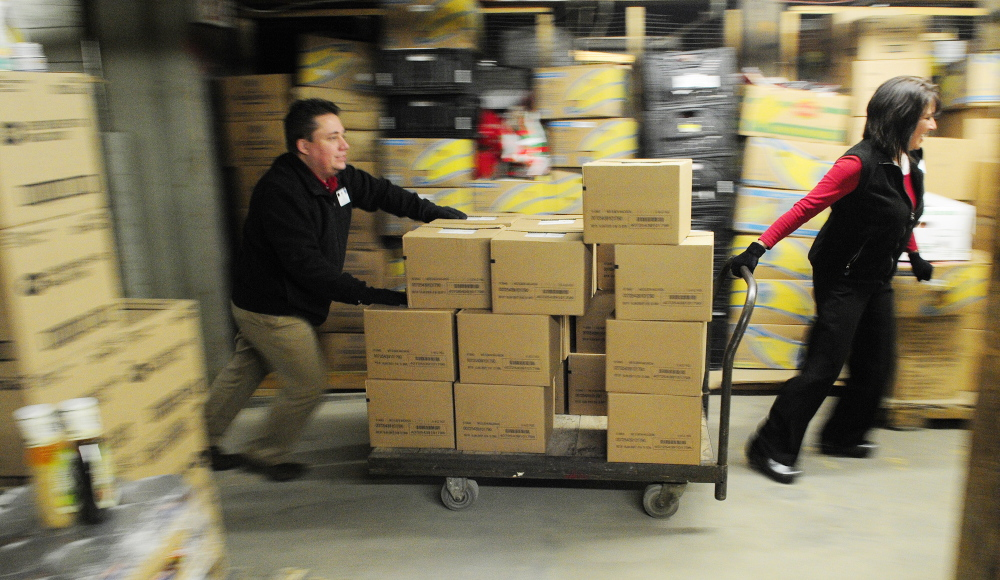 Staff photo by Joe Phelan HELPING HANDS: Hannaford employees Lee Lemar, left, and Marie Tardiff, roll a cart loaded with donated food on Friday February 7, 2014 at the Augusta Food Bank's warehouse.