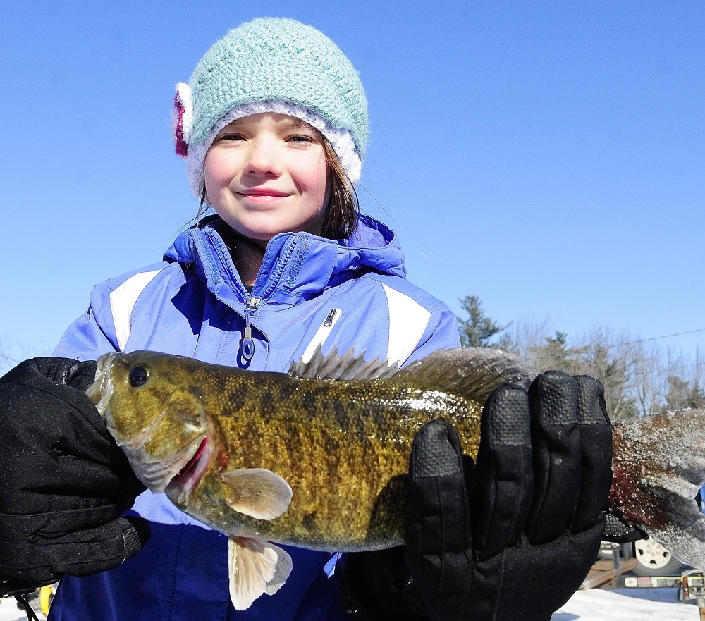 Small girl, big fish: Kathleen Mears, 9, of Brunswick, holds up a 2.19-pound bass she caught Saturday during an RSU 2 fundraiser ice fishing tournament at Cochnewagen Lake Town Landing in Monmouth.