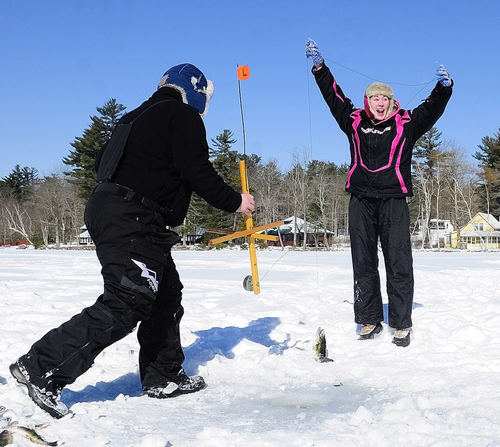 Victory: Collin Acord, left, holds up a trap, while Kyla Johansen, celebrates after pulling up a bass Saturday during an RSU 2 fundraising ice fishing tournament at the Cochnewagen Lake Town Landing in Monmouth.