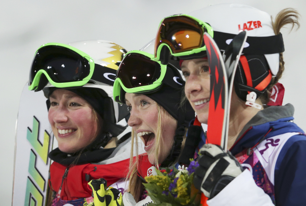 Canada's Justine Dufour-Lapointe, center, celebrates her gold medal in the women's moguls final, with her sister and silver medalist Chloe Dufour-Lapointe, left, and bronze medalist United States' Hannah Kearney, at the Rosa Khutor Extreme Park, at the 2014 Winter Olympics, Saturday, in Krasnaya Polyana, Russia.