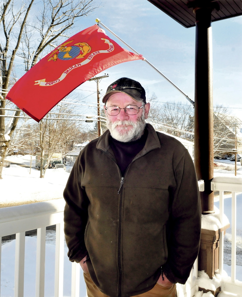 service: A U.S. Marine flag waves beside formerly homeless veteran Steve McFarland at a shelter in Waterville that provides housing for veterans with disabilities.