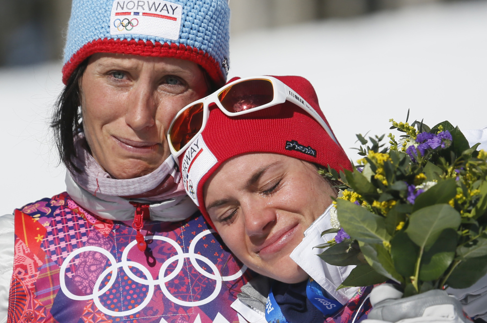 Norway's gold medal winner Marit Bjoergen, left, hugs bronze medal winner Heidi Weng during the flower ceremony of the women's cross-country 15k skiathlon at the 2014 Winter Olympics.