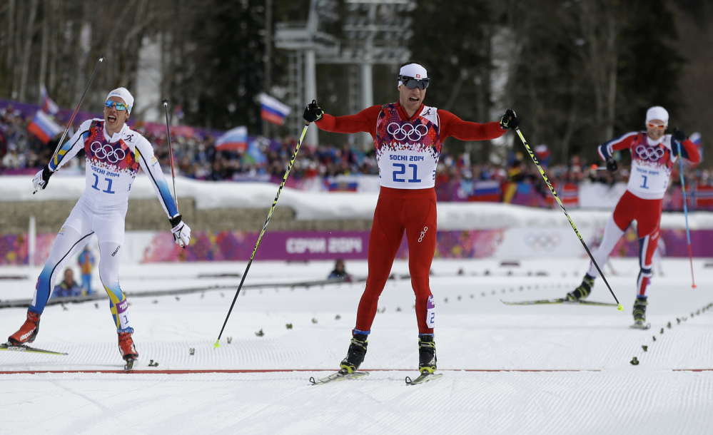 Switzerland's Dario Cologna, center, crosses the finish line to win the men's cross-country 30k skiathlon ahead of Sweden's Marcus Hellner, left, and Norway's Martin Johnsrud Sundby, right, at the 2014 Winter Olympics on Sunday.