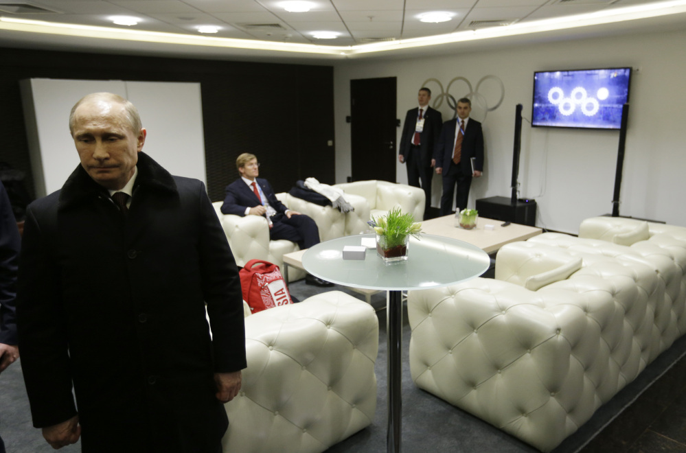 Russian President Vladimir Putin waits in the presidential lounge to be introduced at the opening ceremony of the 2014 Winter Olympics on Friday in Sochi, Russia. Behind him, a TV screen shows four of the Olympic rings opening at the start of the ceremony, while the fifth ring remains closed.