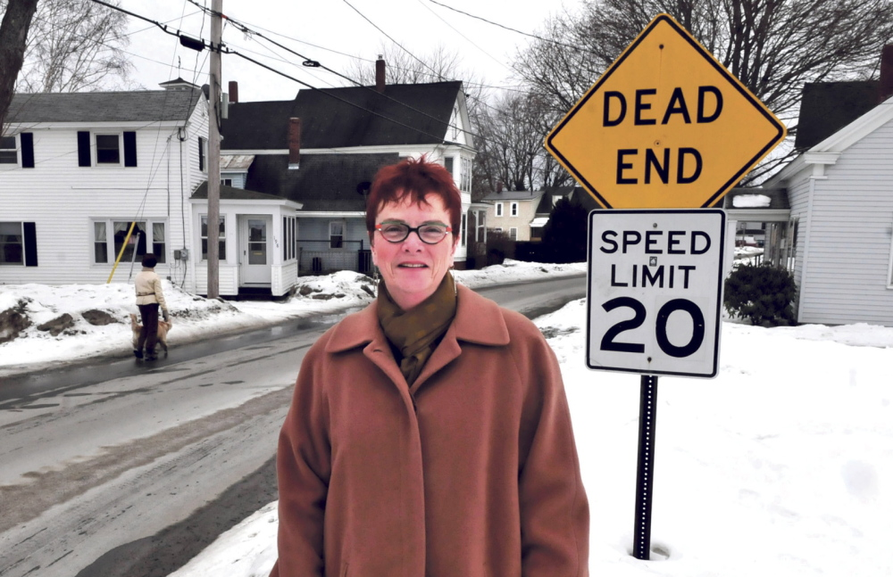 "ROOTS: Author Rhea Cote Robbins stands along Water Street in the South End section of Waterville. Her book ""'down the Plains'"" is about growing up in a home nearby."