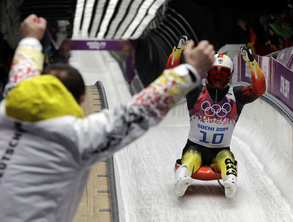 Felix Loch of Germany celebrates as he crosses the finish area to win the gold medal Sunday during the men's singles luge final at the 2014 Winter Olympics in Krasnaya Polyana, Russia.