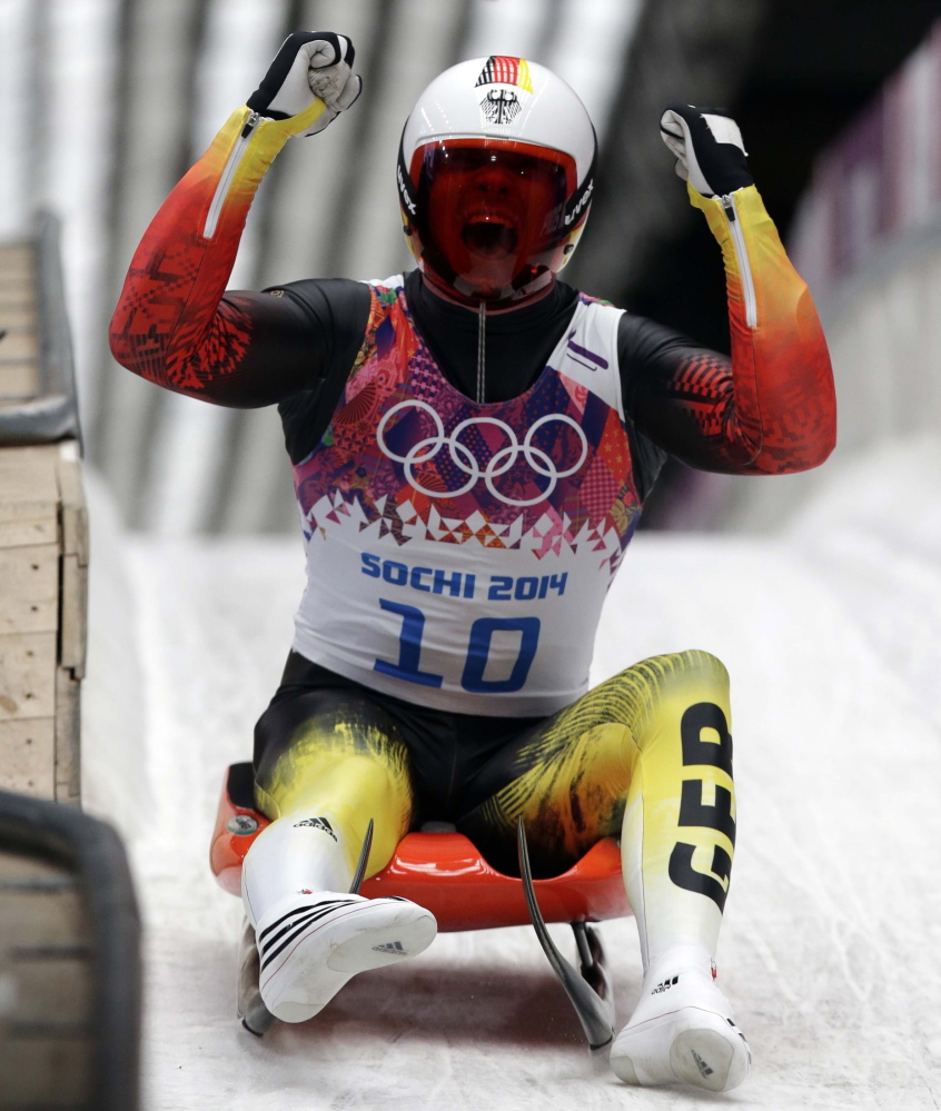 Felix Loch of Germany celebrates as he crosses the finish area to win the gold medal during the men's singles luge final Sunday at the 2014 Winter Olympics in Krasnaya Polyana, Russia.