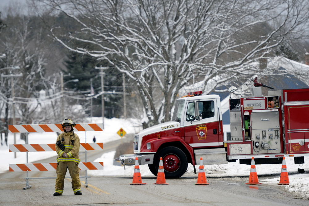 Alfred firefighter and EMT Anna Allard directs traffic away from the York County Courthouse in Alfred on Monday morning after a bomb threat was received.