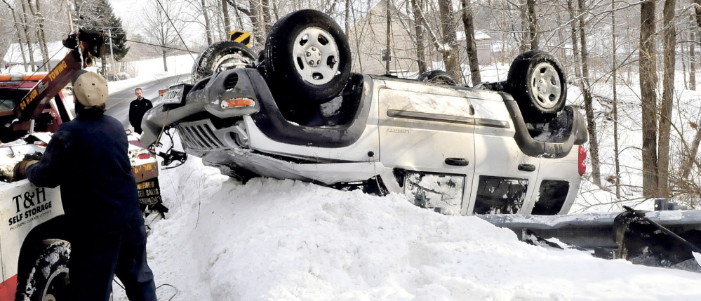 BENTON ROLLOVER: Reid Liberty, background, of Benton, watches as one of two tow truck operators pulls his car out of a ravine after the Jeep slid on ice, went over a guardrail and rolled over into the woods on Route 100 in Benton on Monday. Liberty was not injured.