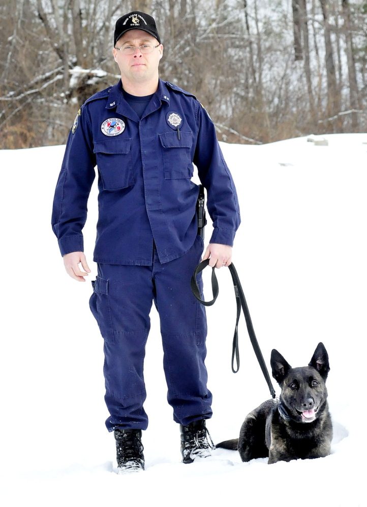 STEADY: Trooper Scott Dalton, a trainer at the Maine State Police K-9 Unit in Vassalboro, stands with his dog Spike during a training exercise on Monday.