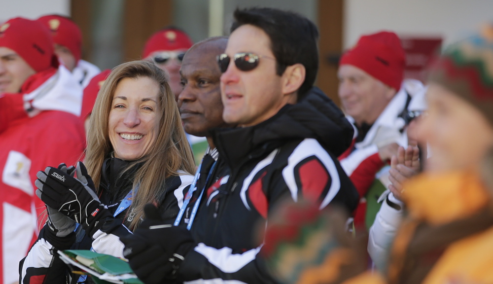 Angelica Morrone di Silvestri, left, and her husband, Gary, center, are representing the Caribbean nation of Dominica in the Olympics. She qualified in a Maine race.